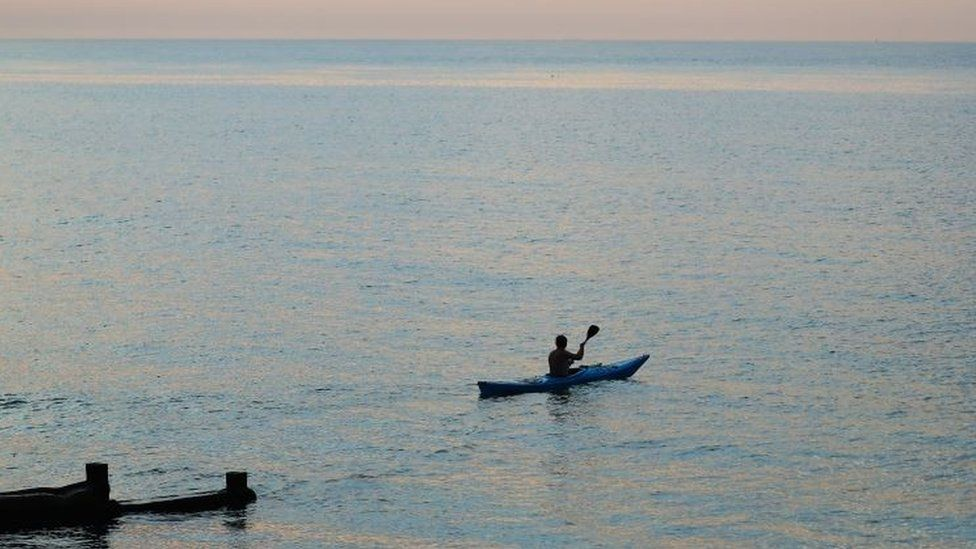 A man kayaks in the sea
