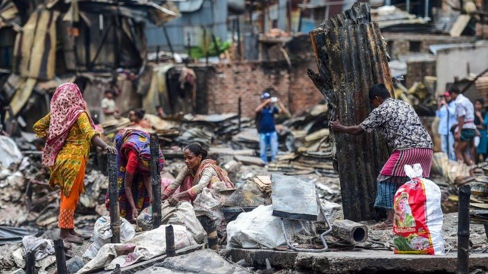 Residents search for household belongings in a slum in Dhaka on 18 August 2019,