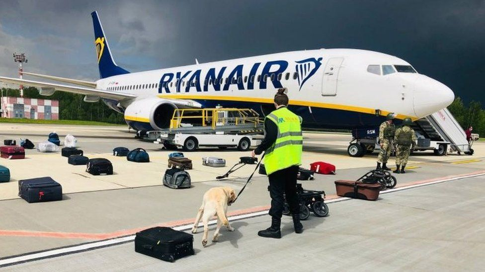 Belarusian security officials with with a sniffer dog checking the luggage of passengers in front of the diverted Ryanair flight at Minsk airport. Photo: 23 May 2021