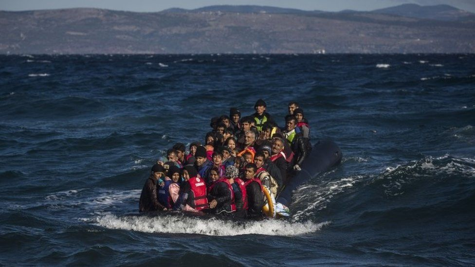 Afghan migrants on an overcrowded inflatable boat approach the Greek island of Lesbos in bad weather after crossing the Aegean see from Turkey, Wednesday, Oct. 28, 2015