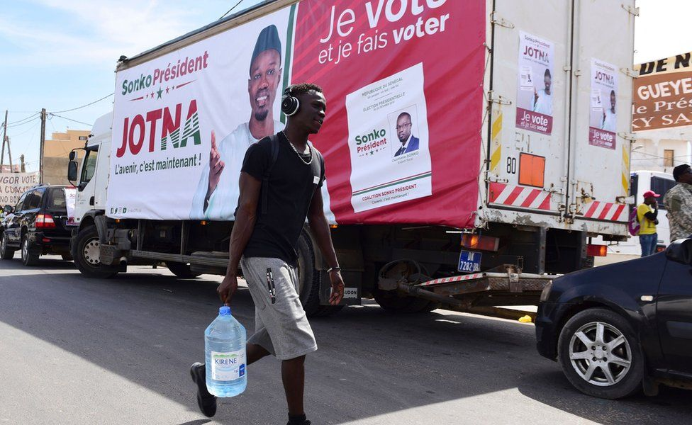 A man walks past a truck with a poster of presidential candidate Ousmane Sonko on 3 February 2019, Dakar, Senegal