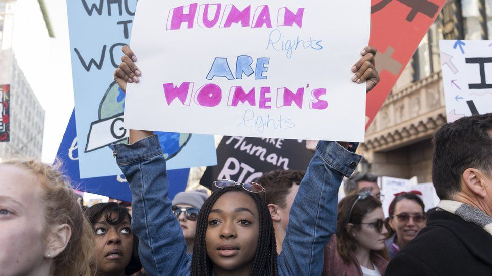 A woman holds a sign in support of women's rights