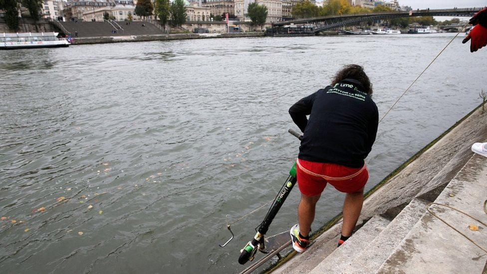 Employees of bicycle-sharing service Lime fish an abandoned electric scooter out of the River Seine in Paris, France