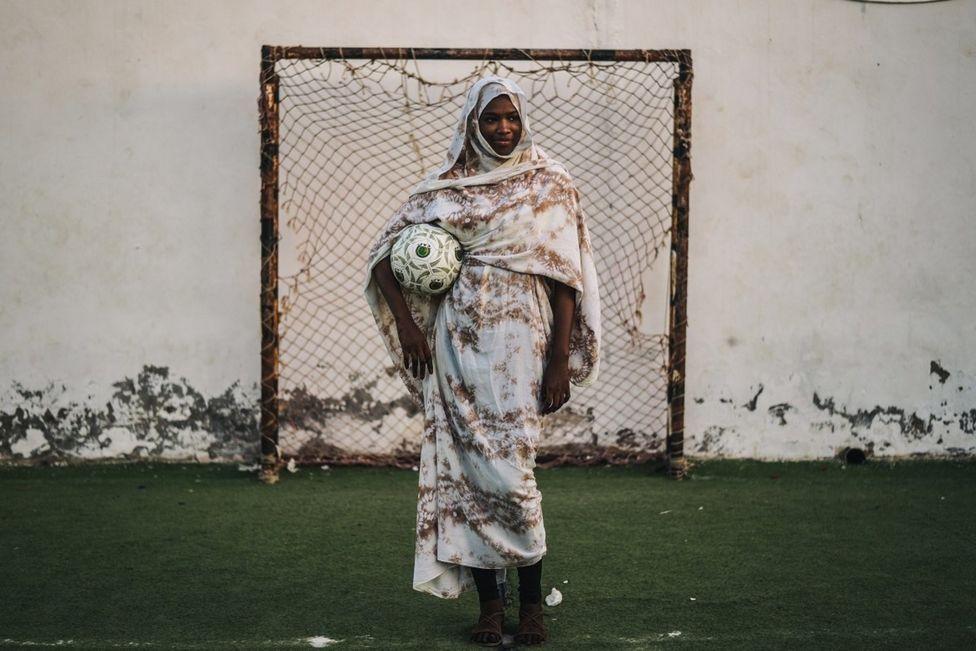 женщина-вратарь в традиционном платье с мячом под мышкой