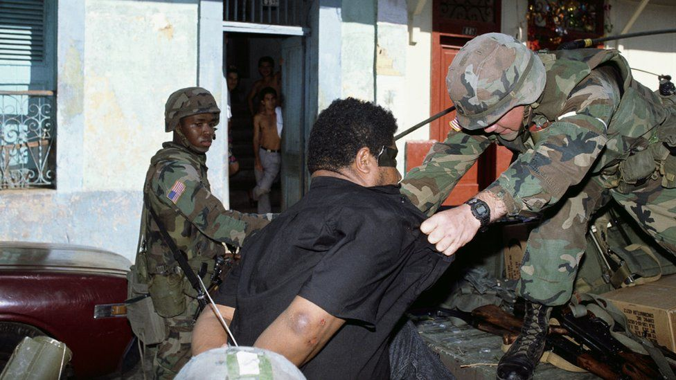 American soldiers detain a man caught looting during the invasion of Panama.