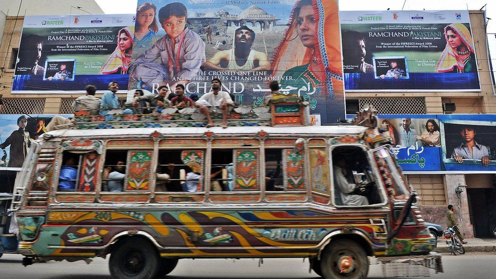 Pakistani men sit on a bus driving past a cinema displaying a billboard of the Indian and Pakistan joint venture movie 'Ramchand Pakistani' in Karachi.