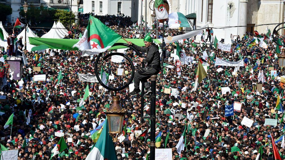 An Algerian protester sits atop a light pole as protesters gather around him