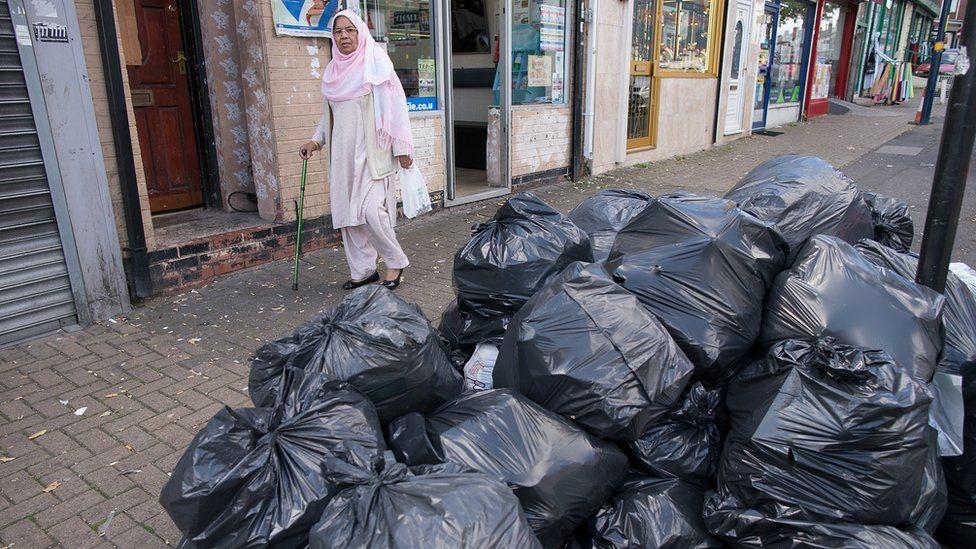 Woman in Alum Rock walks past bin bags