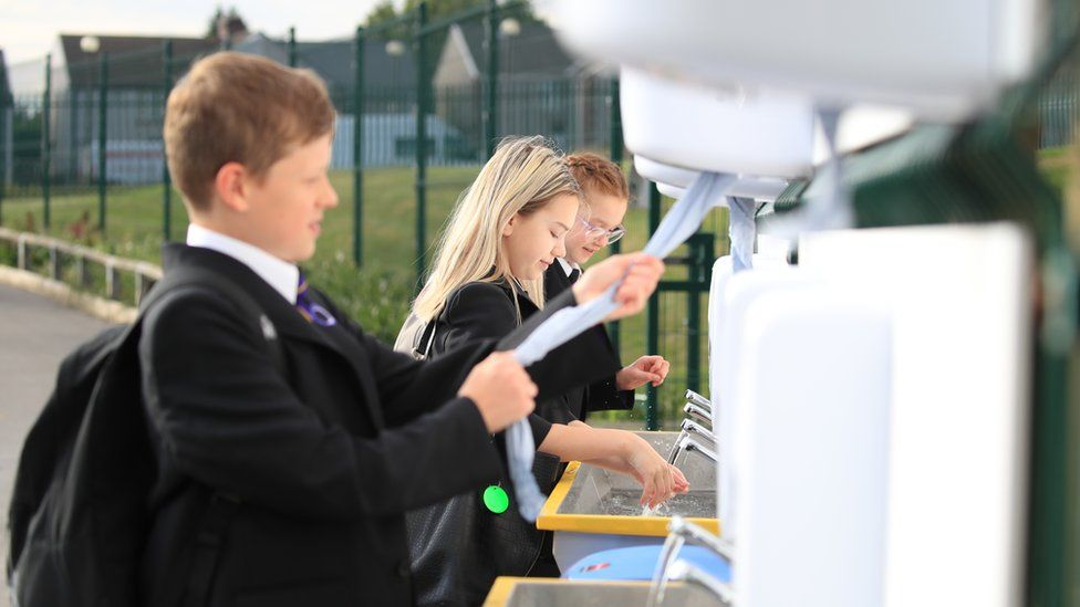 Pupils wash their hands at school