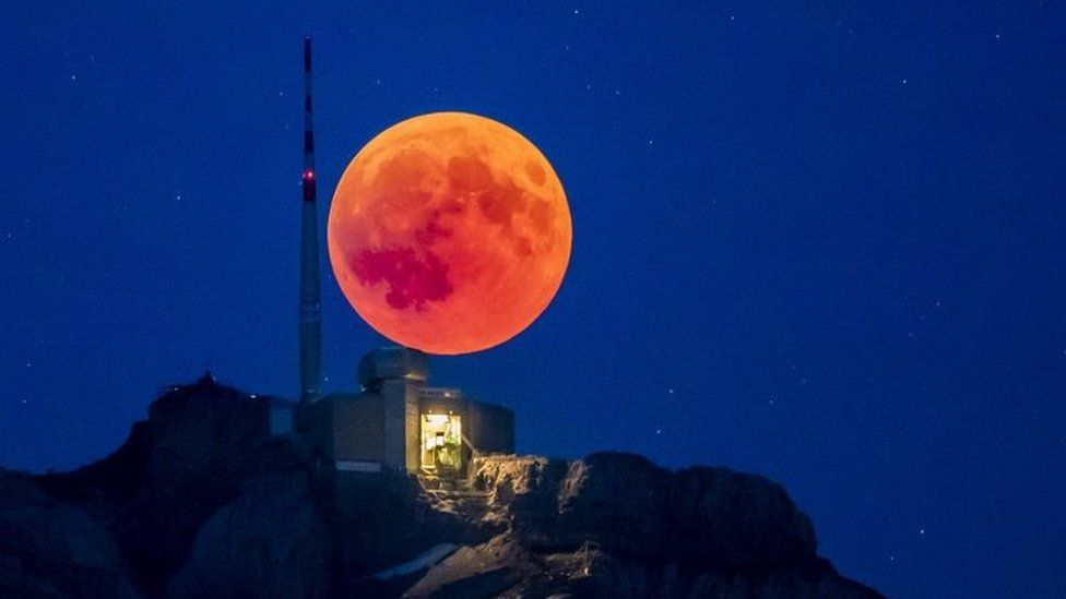 The blood moon rises behind the Saentis (2502m) Alpstein, Canton of Appenzell, Switzerland,