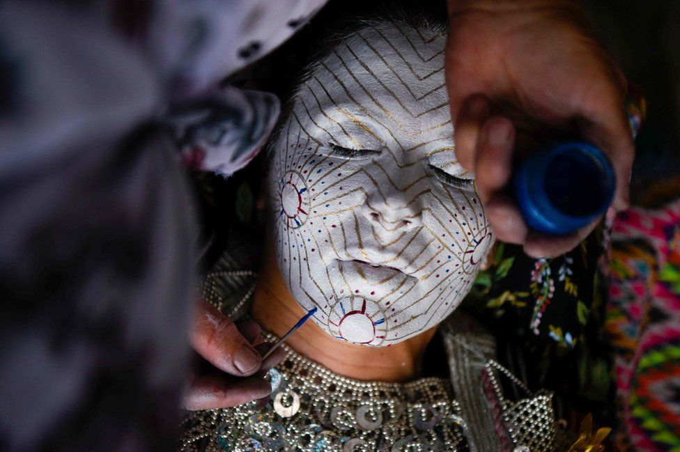 Kosovar woman Sheqerie Buqaj lays on her back as she receives a traditional face painting