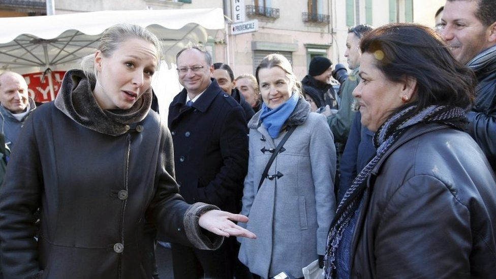 Marion Marechal-Le Pen, left, argues with a woman as she campaigns at the Saint-Siffrein fair in Carpentras