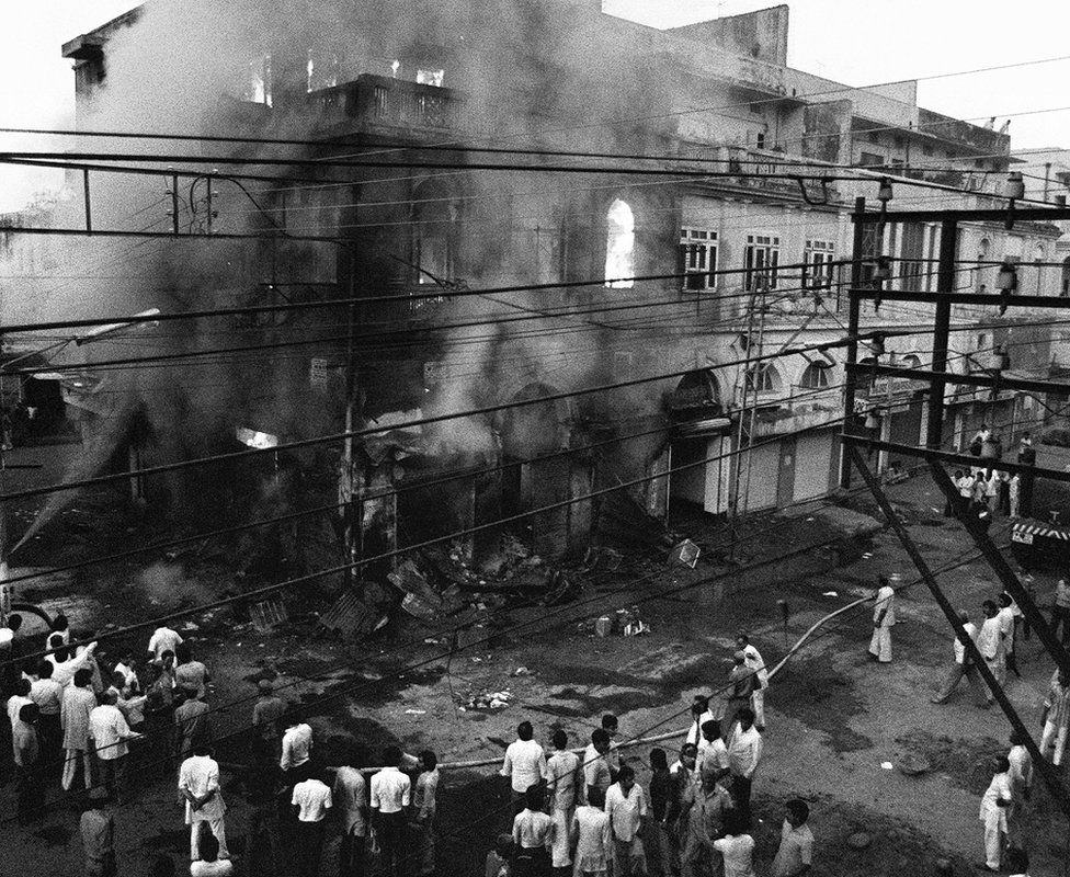 People watch as a building belonging to Sikhs burns in Delhi. Photo: 2 November 1984