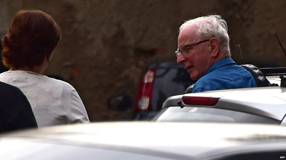 Pat Hickey (R) arrives at a police station in Rio de Janeiro, Brazil, 18 August