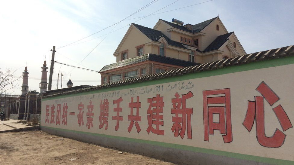 A propaganda slogan in Chinese and Arabic in Weizhou. It reads, 'A unified national family joins hands to build a new Tongxin County'