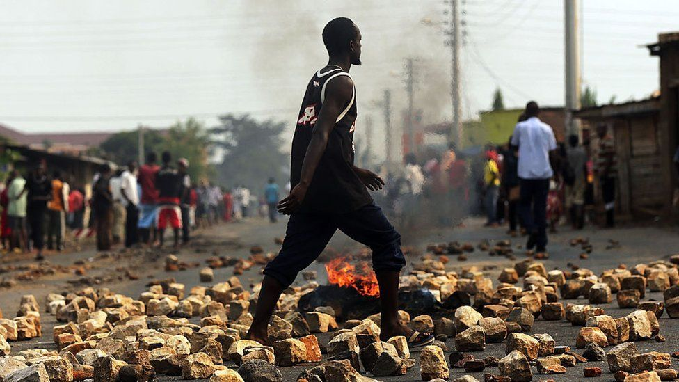 A man walks through paving stones and a tire fire during protests against the governing party on June 26, 2015 in Bujumbura, Burundi