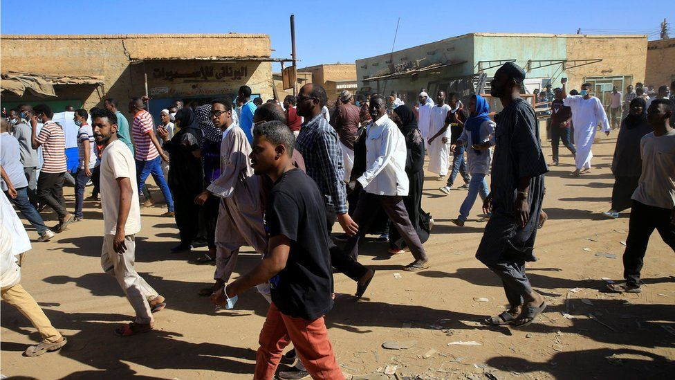 Sudanese demonstrators march along the street during anti-government protests after Friday prayers