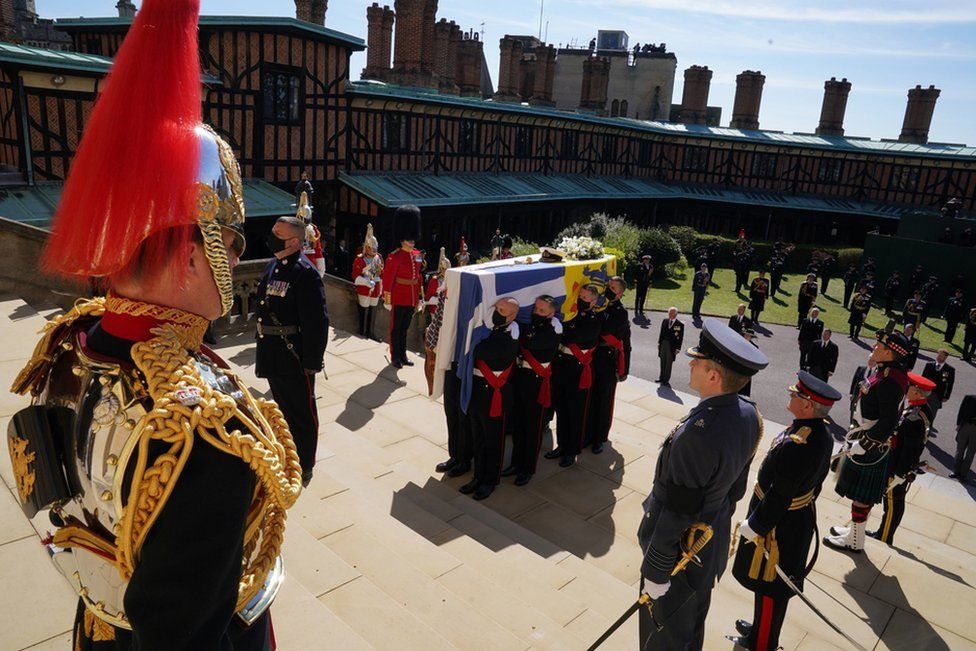 The Duke of Edinburgh's coffin, covered with his Personal Standard, is carried into St George's Chapel, Windsor Castle, Berkshire, ahead of the funeral of the Duke of Edinburgh. April 17, 2021.