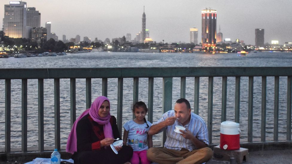 A family eating on a bridge over the Nile River in Cairo Egypt