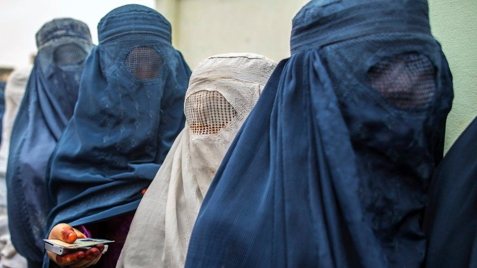 Afghan women wait to cast their ballot at a polling station dressed in blue and white burkas