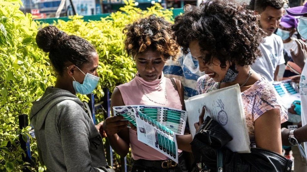 People hold a paper that shows a list of political parties in Addis Ababa, Ethiopia, on June 17, 2021, who are running for the upcoming June 21, 2021 elections