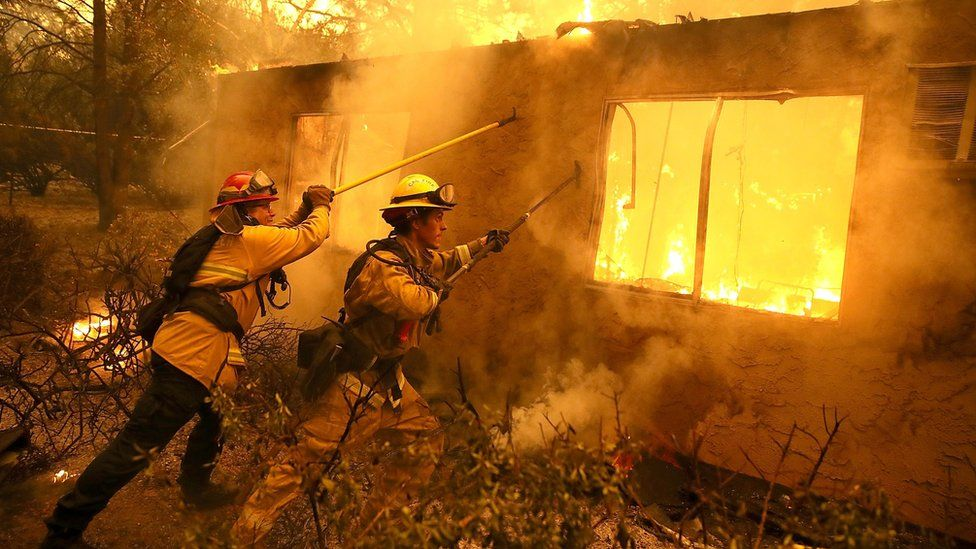 Firefighters try to keep flames from burning home from spreading to a neighbouring apartment complex as they battle the Camp Fire on November 9, 2018 in Paradise, California