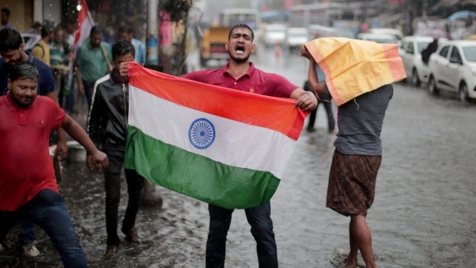 An Indian man holds up an Indian flag in celebration after Indian said it targeted militants in Pakistan