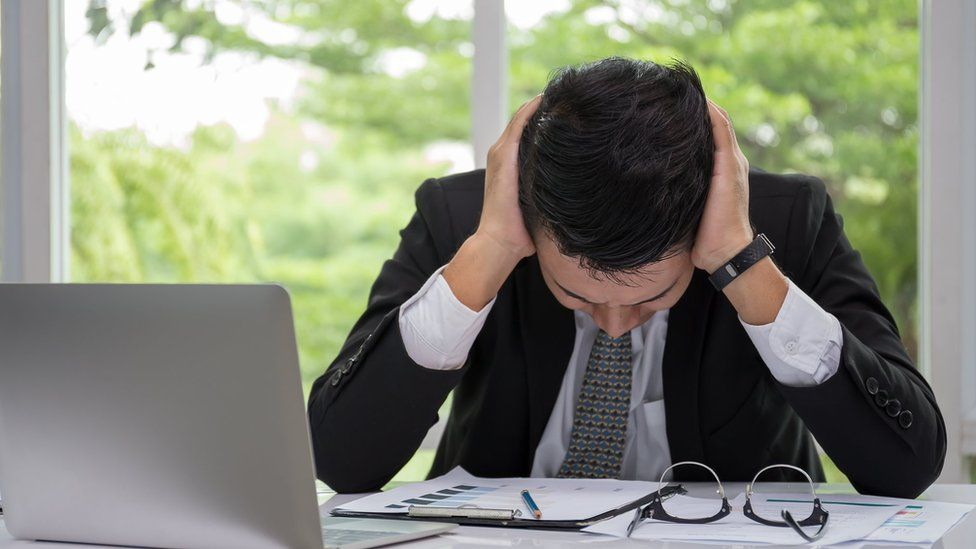 File photo: A stressed worker by his laptop