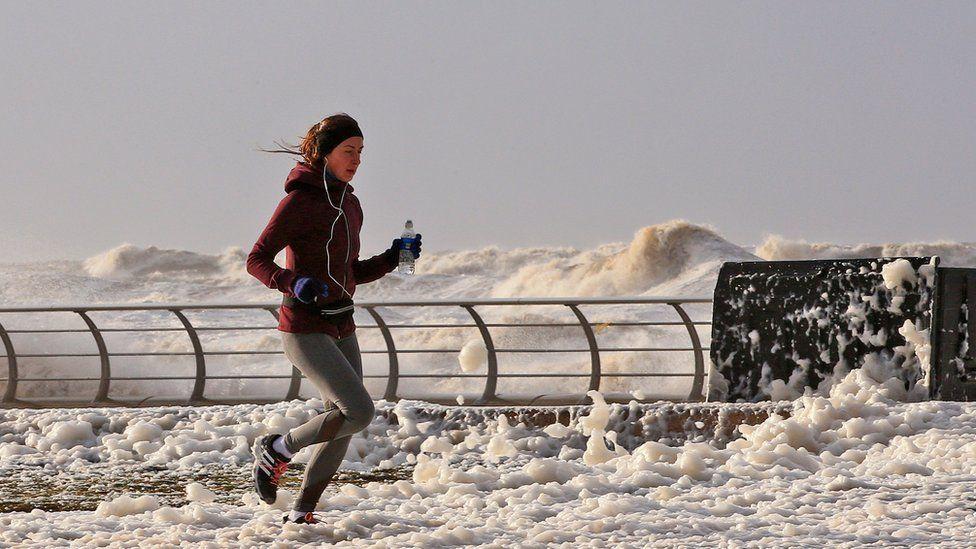 Woman running in sea foam in Blackpool, after Storm Eleanor