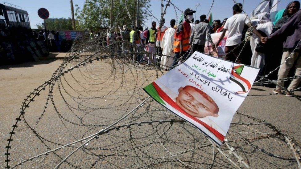 A flyer bearing an image of Ahmed al-Khair, a detained Sudanese demonstrator who died while in custody, hangs on barbed wire as people gather in front of a court in Omdurman, near the capital Khartoum, Sudan, 30 December 2019