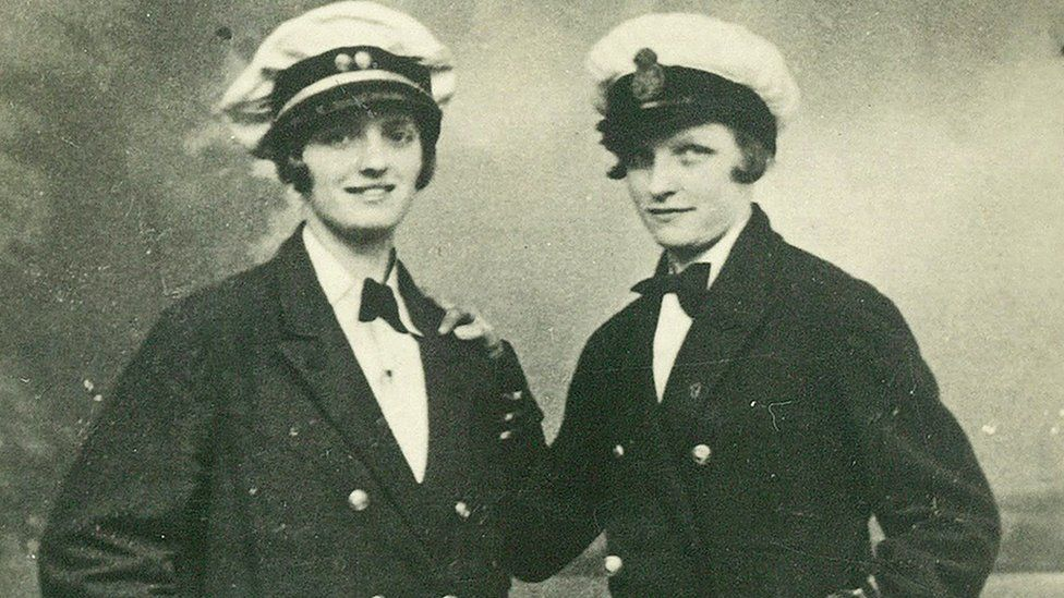Two women dressed as Navy officers