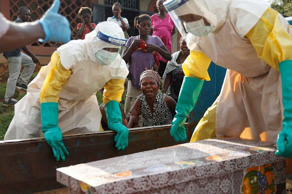A mother of a child who died from suspected Ebola, cries near her child's coffin