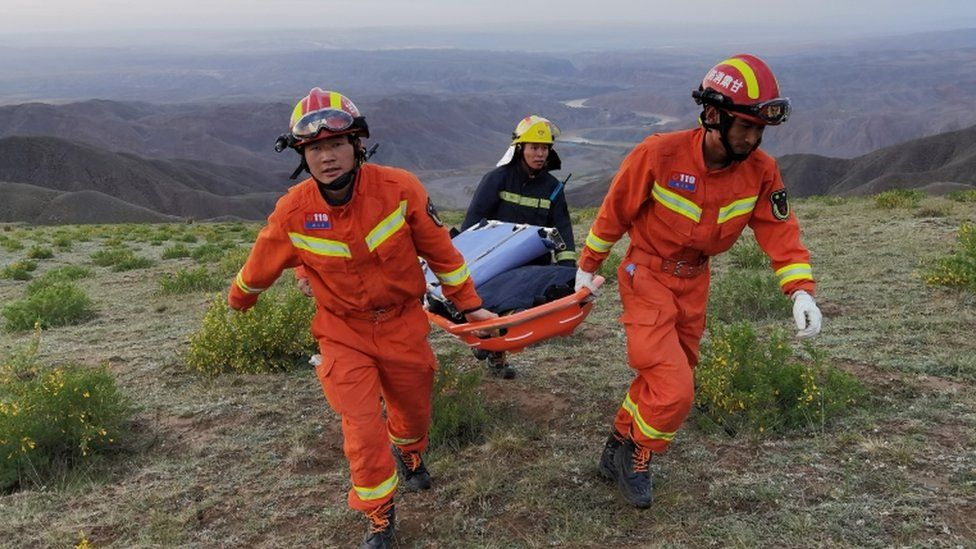 Rescue workers carry a stretcher as they work at the site where extreme cold weather killed participants of an 100-km ultramarathon race in Baiyin, Gansu province.