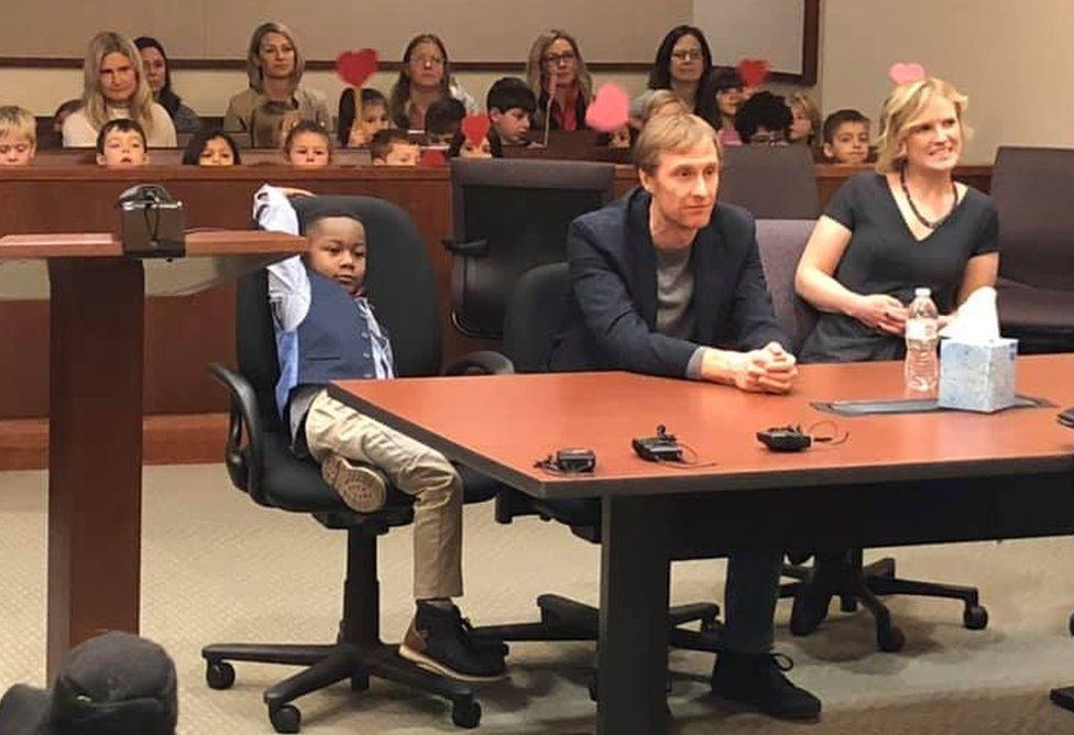 A picture shared by Kent County, Michigan's Facebook page shows a little boy named Michael being formally adopted in court, watched by his Kindergarten classmates