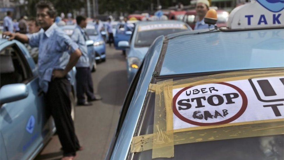 A taxi with a sign saying 'Top Uber/Grab' in Jakarta