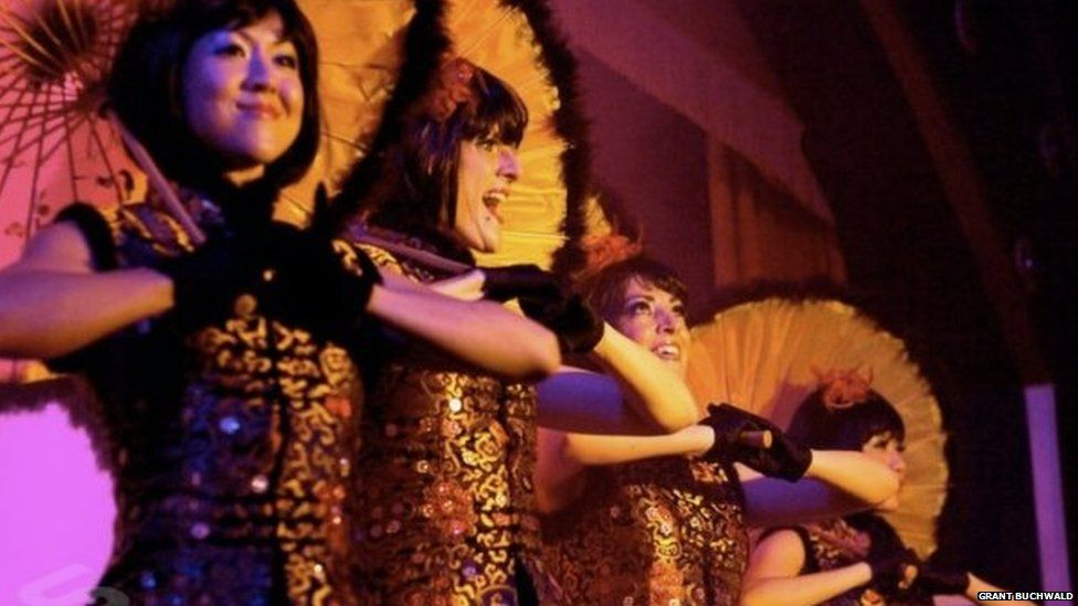 Showgirls perform with parasols