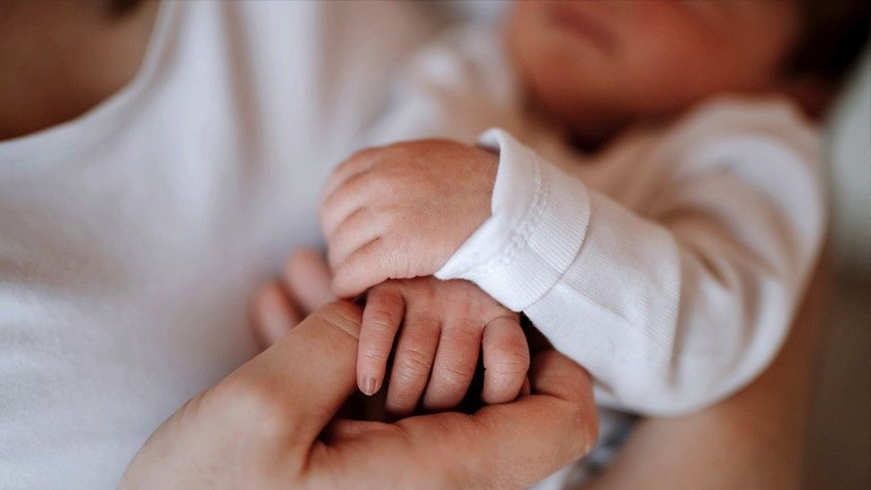 File image of a baby holding an adult's hand