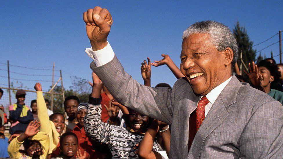 Nelson Mandela holding his fist up