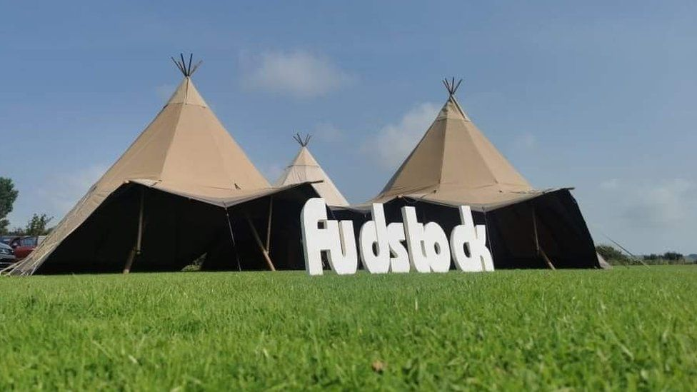 A Fudstock sign and tents in a field