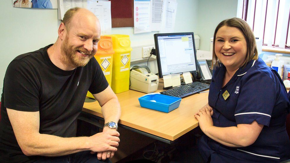 Aled Richards with a nurse sitting at a desk