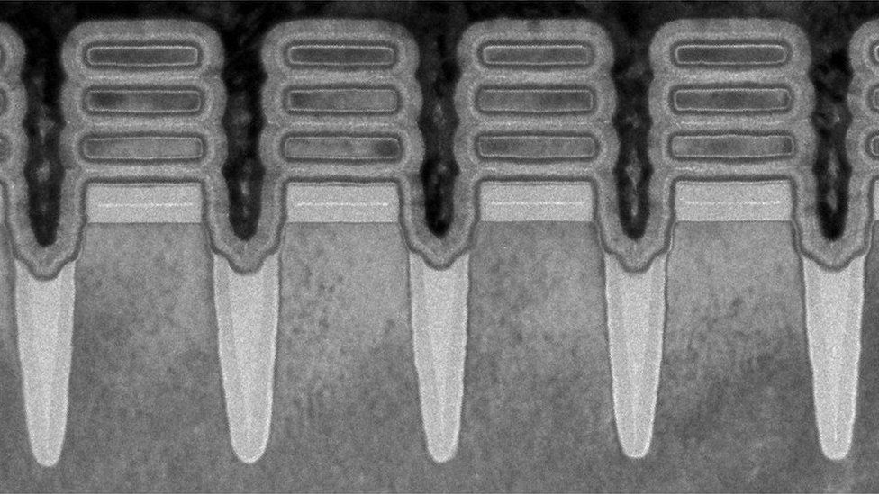 """A microspcope image in black and white shows what appear to be four upright pillars with three floating """"discs"""" at their top - a view of the transistors"""