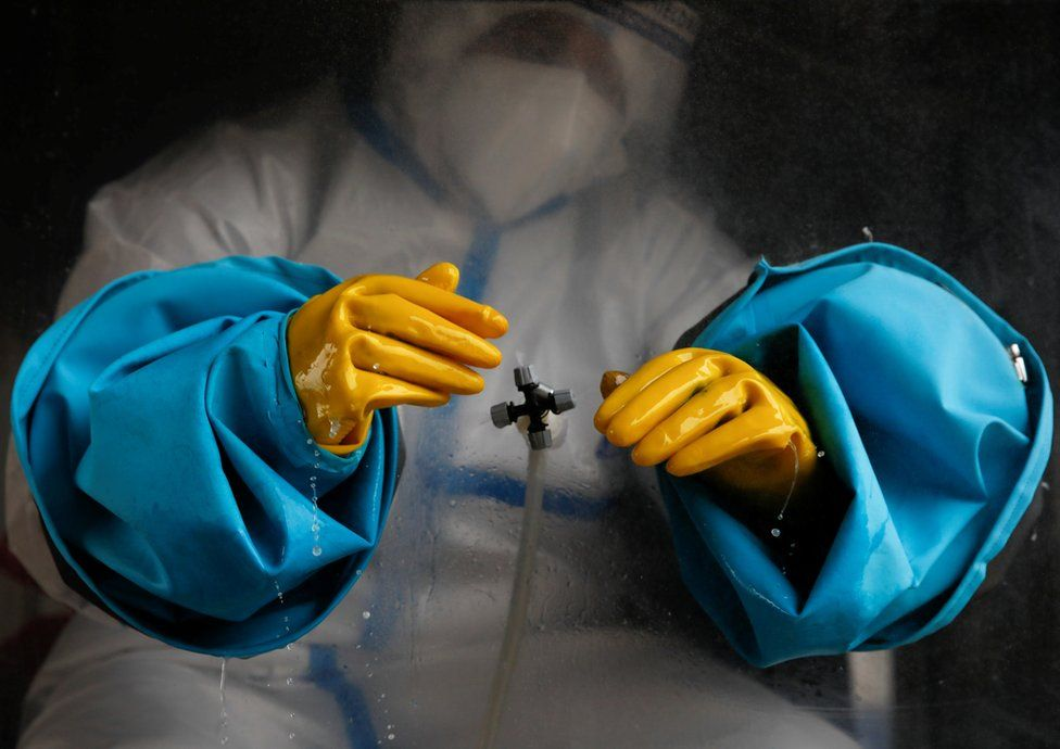 A health worker wearing PPE disinfects their hands in Kathmandu, Nepal