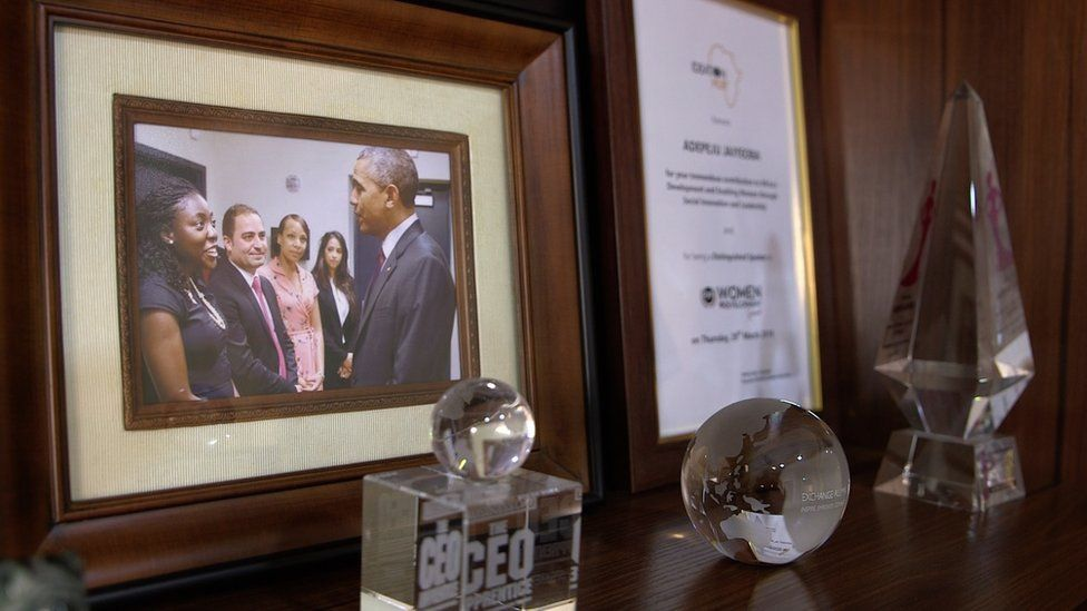 A desk with awards and a picture of Peju with President Obama
