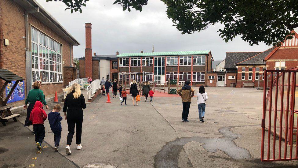 Parents taking their children to school