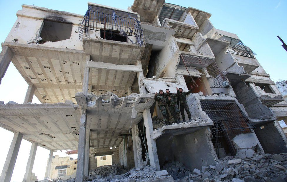 Members of the Syrian pro-government forces pose for a picture in a destroyed building in Salma, in Latakia province in January 2016, following its recapture from rebel fighters