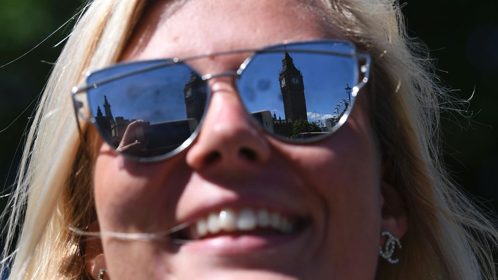 Houses of parliament reflected in woman's sunglasses