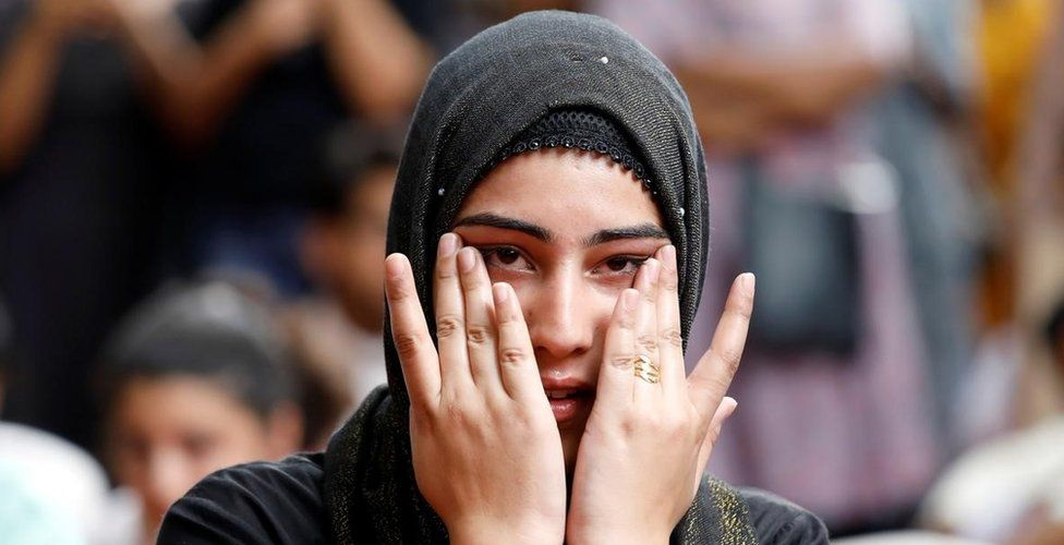 A Kashmiri woman wipes her tears while listening to a story of a Kashmiri man at a function in New Delhi where compatriots gathered to observe Eid.