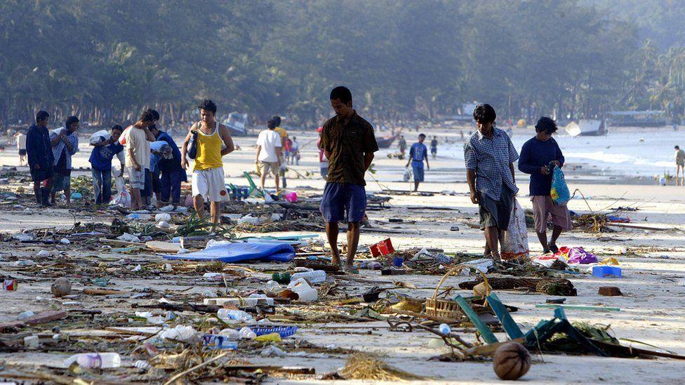 People walk through debris along the shoreline of Patong beach of Phuket island, southern Thailand, 27 December 2004