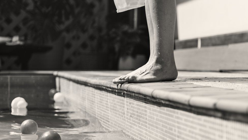 Feet by a swimming pool