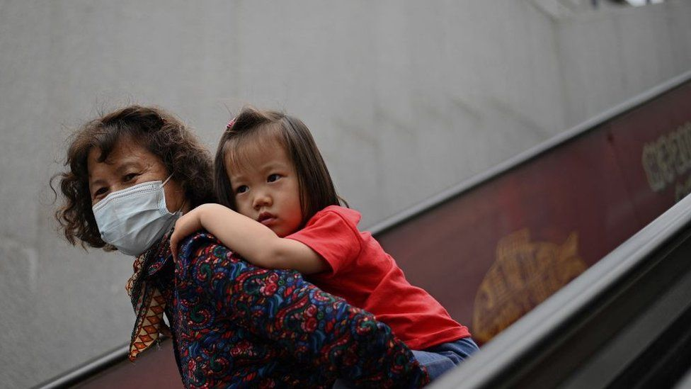 A girl rides on the back of a woman down an escalator at a shopping centre on International Children's Day in Beijing